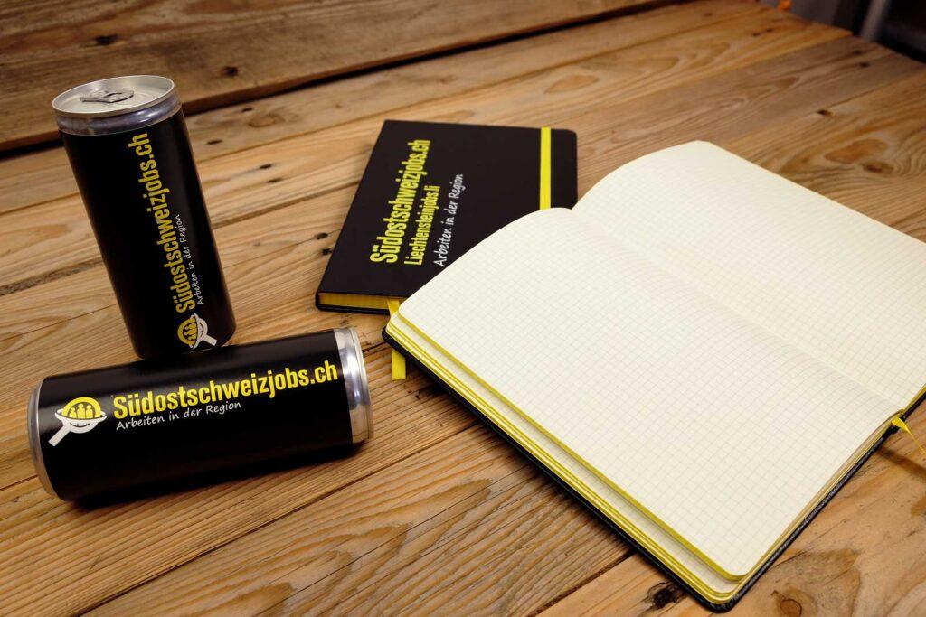 Notizbücher sowie Energydrink Dosen für Südostschweizjobs.ch